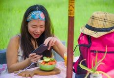 Νέα ευτυχής και αρκετά ψηφιακή ασιατική κορεατική γυναίκα νομάδων που παίρνει την εικόνα της σαλάτας φρούτων με την κινητή τηλεφω Στοκ Φωτογραφία