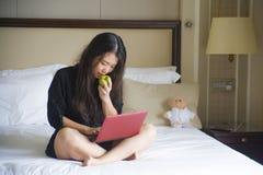 Νέα ευτυχής και χαλαρωμένη ασιατική κινεζική γυναίκα στο κρεβάτι δωματίου ξενοδοχείου που λειτουργεί με το φορητό προσωπικό υπολο στοκ εικόνα με δικαίωμα ελεύθερης χρήσης
