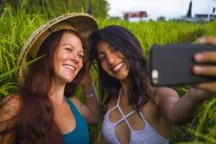 Νέα ευτυχής και όμορφη λατινική καυκάσια γυναίκα κοριτσιών iand στο παραδοσιακό ασιατικό καπέλο αγροτών που παίρνει τις φίλες sel στοκ εικόνα