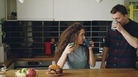 Νέα ευτυχής καυκάσια ερωτευμένη συνεδρίαση των ζευγών το πρωί στη σύγχρονη κουζίνα στον πίνακα για να έχει το πρόγευμα από κοινού φιλμ μικρού μήκους