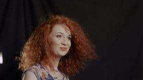Νέα ευτυχής κόκκινη γυναίκα με τον αέρα στην τρίχα φιλμ μικρού μήκους