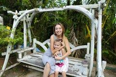 Νέα ευτυχής μητέρα με την κόρη που οδηγά στην ταλάντευση στον εξωτικό κήπο, φοίνικες στο υπόβαθρο στοκ εικόνα