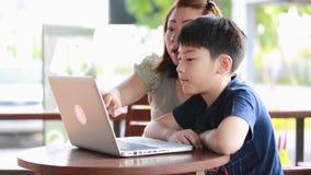 Νέα, ευτυχής μητέρα με το παιδί που χρησιμοποιεί το lap-top στο πεζούλι απόθεμα βίντεο