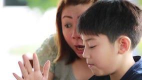 Νέα, ευτυχής μητέρα με το παιδί που χρησιμοποιεί το lap-top στο πεζούλι φιλμ μικρού μήκους
