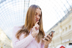 Νέα ευτυχής ξανθή γυναίκα που διαβάζει ένα μήνυμα στο τηλέφωνο στοκ εικόνα