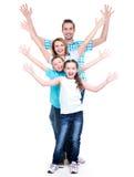 Νέα ευτυχής οικογένεια με αυξημένα τα παιδιά χέρια επάνω Στοκ Εικόνες