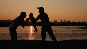 Νέα ευτυχής οικογένεια: παιχνίδι πατέρων, μητέρων και μωρών στον ποταμό στο ηλιοβασίλεμα Ηλιοβασίλεμα σκιαγραφιών φιλμ μικρού μήκους