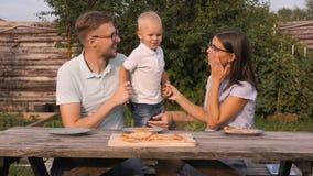 Νέα ευτυχής οικογένεια που έχει το πικ-νίκ στον κήπο Mom, μπαμπάς και γιος που τρώνε την πίτσα υπαίθρια απόθεμα βίντεο