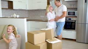 Νέα ευτυχής οικογένεια που κινείται προς το νέο διαμέρισμα Δύο μικρά κορίτσια που τρέχουν στο νέο σπίτι με τους γονείς στο χαρτόν απόθεμα βίντεο