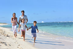 Νέα ευτυχής οικογένεια που τρέχει στην παραλία που έχει τη διασκέδαση Στοκ Φωτογραφίες