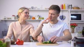 Νέα ευτυχής οικογένεια που φλερτάρει, μαγειρεύοντας σαλάτα των ακατέργαστων λαχανικών, υγιή τρόφιμα eco απόθεμα βίντεο