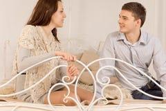 Νέα ευτυχής συνεδρίαση ζευγών που κουβεντιάζει σε ένα κρεβάτι στοκ εικόνες