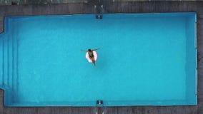 Νέα ευτυχής χαλάρωση γυναικών στο διογκώσιμο παιχνίδι λιμνών στην μπλε πισίνα την ηλιόλουστη ημέρα απόθεμα βίντεο