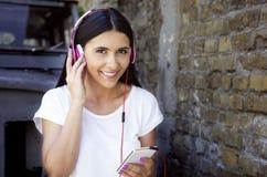 Νέα ευτυχής χαμογελώντας γυναίκα με τα ακουστικά και το τηλέφωνο Στοκ Εικόνα