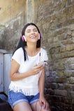 Νέα ευτυχής χαμογελώντας γυναίκα με τα ακουστικά Να καθίσει υπαίθρια στο καλοκαίρι Στοκ Εικόνες