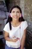 Νέα ευτυχής χαμογελώντας γυναίκα με τα ακουστικά Στοκ φωτογραφία με δικαίωμα ελεύθερης χρήσης