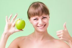 Νέα ευτυχής χαμογελώντας γυναίκα με το μήλο και τους αντίχειρες επάνω στοκ φωτογραφίες