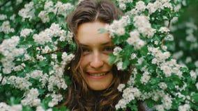 Νέα ευτυχής χαμογελώντας πράσινος-eyed γυναίκα με τα λουλούδια που εξετάζει τη κάμερα ομορφιά φυσική απόθεμα βίντεο