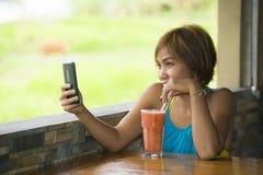 Νέα ευτυχής όμορφη ασιατική γυναίκα στη καφετερία που χρησιμοποιεί Διαδίκτυο app στο κινητό τηλέφωνο που πίνει τον υγιή χυμό φρού Στοκ φωτογραφία με δικαίωμα ελεύθερης χρήσης