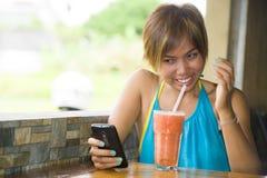 Νέα ευτυχής όμορφη ασιατική γυναίκα στη καφετερία που χρησιμοποιεί Διαδίκτυο app στο κινητό τηλέφωνο που πίνει τον υγιή χυμό φρού Στοκ Εικόνα