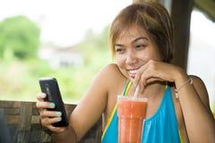 Νέα ευτυχής όμορφη ασιατική γυναίκα στη καφετερία που χρησιμοποιεί Διαδίκτυο app στο κινητό τηλέφωνο που πίνει τον υγιή χυμό φρού Στοκ Φωτογραφία