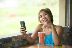 Νέα ευτυχής όμορφη ασιατική γυναίκα στη καφετερία που χρησιμοποιεί Διαδίκτυο app στο κινητό τηλέφωνο που πίνει τον υγιή χυμό φρού Στοκ φωτογραφίες με δικαίωμα ελεύθερης χρήσης