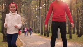Νέα ευτυχή κορίτσια που τρέχουν στο δρόμο στο πάρκο φθινοπώρου μαζί σε σε αργή κίνηση απόθεμα βίντεο