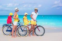 Νέα ευτυχή οικογενειακά οδηγώντας ποδήλατα σε τροπικό Στοκ Φωτογραφία