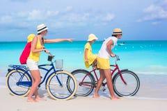 Νέα ευτυχή οικογενειακά οδηγώντας ποδήλατα σε τροπικό Στοκ Εικόνες