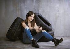 Νέα, εύθυμη γυναίκα με τα ακουστικά που κάθεται κοντά στις ρόδες και Στοκ Εικόνες