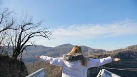 Νέα εύθυμη γυναίκα που αυξάνει τα όπλα της στο skybridge μπροστά από την όμορφη κορυφή βουνών πέρα από το χρυσό ουρανό ηλιοβασιλέ απόθεμα βίντεο