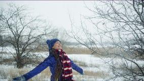 Νέα εύθυμη γυναίκα που ρίχνει επάνω στο χιόνι απόθεμα βίντεο