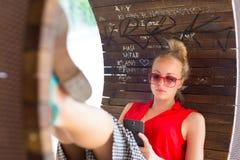 Νέα εύθυμη γυναίκα που χρησιμοποιεί το smarthphone Στοκ Φωτογραφία