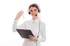 Νέα εύθυμη επιχειρησιακή κυρία με το ακουστικό και μικρόφωνο που κοιτάζει μακριά και που χαμογελά που απομονώνεται στο άσπρο υπόβ Στοκ εικόνες με δικαίωμα ελεύθερης χρήσης