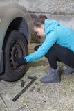 Νέα ελαστικά αυτοκινήτου αυτοκινήτων αλλαγών οδηγών γυναικών Στοκ Εικόνα