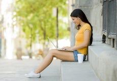 Νέα ελκυστική λατινική γυναίκα στα καθιερώνοντα τη μόδα περιστασιακά ενδύματα που μελετούν ή που λειτουργούν στο φορητό προσωπικό Στοκ Εικόνες