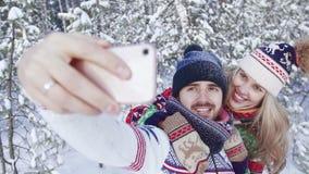 Νέα ελκυστική γυναίκα και νέος χαμογελώντας άνδρας που παίρνουν την όμορφη φωτογραφία στο χειμερινό δάσος απόθεμα βίντεο