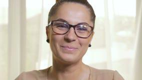 Νέα ελκυστική γυναίκα με τα γυαλιά που φλερτάρουν και που φυσούν το φιλί απόθεμα βίντεο