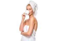 Νέα ελκυστική γυναίκα με τα μπλε μάτια στα ποτά πετσετών Στοκ Εικόνες