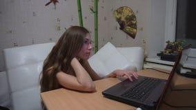 Νέα ελκυστική γυναίκα που δακτυλογραφεί χαρωπά στο lap-top της στο σπίτι απόθεμα βίντεο