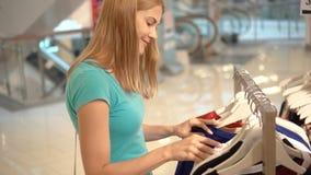 Νέα ελκυστική γυναίκα που επιλέγει τα ενδύματα στο κατάστημα Ψωνίζοντας στη λεωφόρο, χρόνος πωλήσεων Έννοια καταναλωτισμού απόθεμα βίντεο