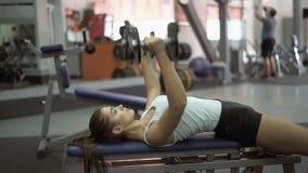 Νέα ελκυστική γυναίκα που εργάζεται σκληρά στη γυμναστική απόθεμα βίντεο