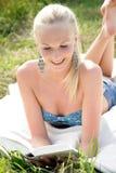 Νέα ελκυστική γυναίκα που διαβάζει ένα βιβλίο Στοκ Φωτογραφία