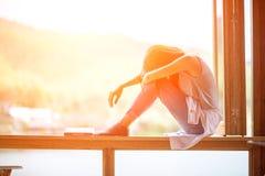 Νέα ελκυστική γυναίκα, που κάθεται σε ένα παράθυρο στοκ φωτογραφία με δικαίωμα ελεύθερης χρήσης