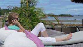 Νέα ελκυστική γυναίκα που μιλά στο τηλέφωνο στην πισίνα στο τροπικό θέρετρο απόθεμα βίντεο