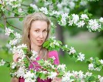 Κήπος Apple-δέντρων την άνοιξη και νέα γυναίκα ο ξανθός μεταξύ των δέντρων Στοκ εικόνες με δικαίωμα ελεύθερης χρήσης