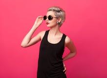 Νέα ελκυστική γυναίκα που φορά γύρω από τα γυαλιά ηλίου πέρα από το ρόδινο υπόβαθρο χρώματος Στοκ Φωτογραφία