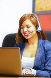 Νέα ελκυστική γυναίκα που φορά τη συνεδρίαση ενδυμάτων και κασκών γραφείων από το γραφείο που εξετάζει τη οθόνη υπολογιστή, που λ Στοκ εικόνες με δικαίωμα ελεύθερης χρήσης