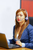Νέα ελκυστική γυναίκα που φορά τη συνεδρίαση ενδυμάτων και κασκών γραφείων από το γραφείο που εξετάζει τη οθόνη υπολογιστή, που λ Στοκ φωτογραφία με δικαίωμα ελεύθερης χρήσης