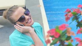 Νέα ελκυστική γυναίκα που χρησιμοποιεί το τηλέφωνο κυττάρων της στις διακοπές κοντά στη λίμνη απόθεμα βίντεο